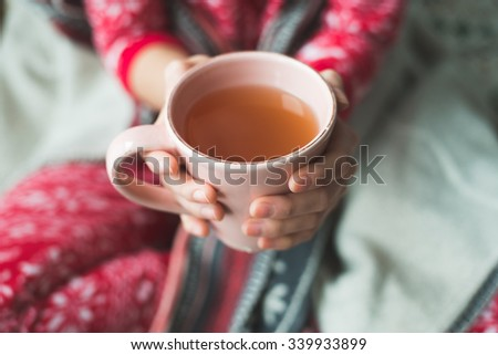 Young woman relaxing in bed with a cup of tea - stock photo