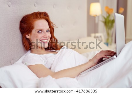 Young woman relaxing in bed with her laptop as she spends a lazy weekend at home turning to smile at the camera - stock photo
