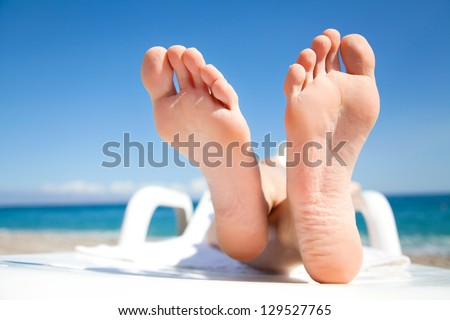 Young woman relaxing in chaise longue on the beach - stock photo