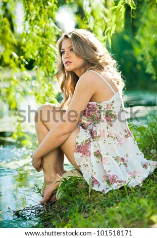 Young woman relaxing in dress  on the shore of lake. - stock photo