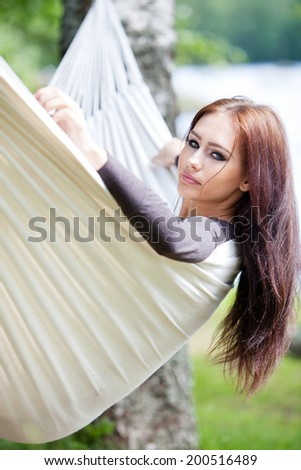 Young woman relaxing in hammock - stock photo