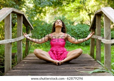 young woman relaxing in nature sitting on wooden bridge