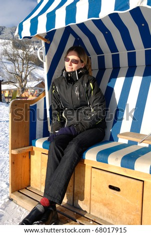 Young woman relaxing in roofed wicker beach chair on a sunny winter day in austria. - stock photo