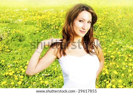 young woman relaxing in the grass and flowers - stock photo