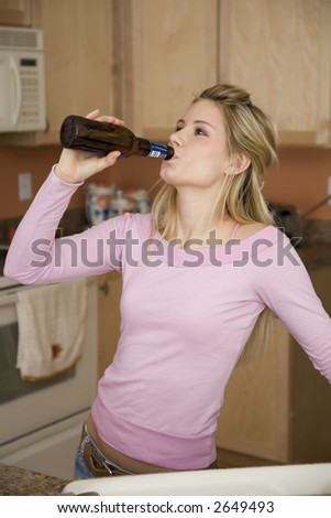 Young woman relaxing in the kitchen drinking a beer  Underage drinking