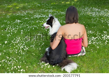 Young woman relaxing in the park with her border collie dog, with her back towards the camera - stock photo