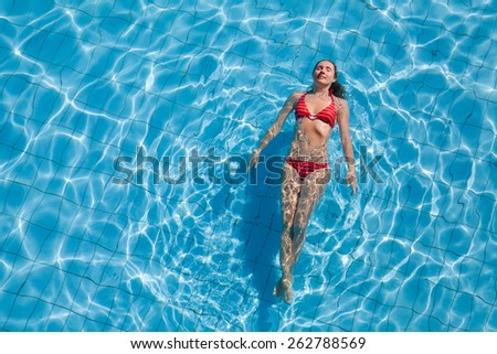 Young woman relaxing in the swimming pool - stock photo