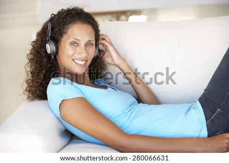 Young Woman Relaxing Listening To Music At Home - stock photo