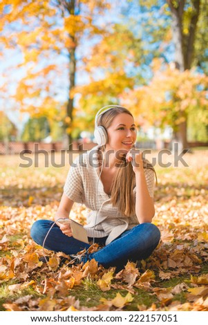 Young woman relaxing listening to music on her headphones as she sits cross-legged on the ground in an autumn park with her MP3 player - stock photo