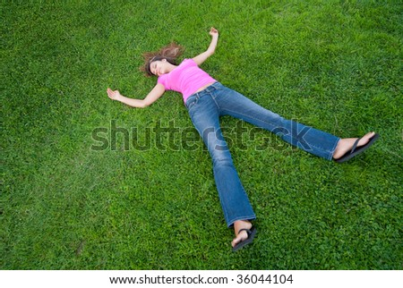 Young Woman relaxing lying on green grass - stock photo