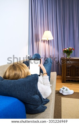Young woman, relaxing on a couch with an electronic tablet. Her shoes on the carpet next to the sofa, and the curtains closed behind an antique chest - stock photo