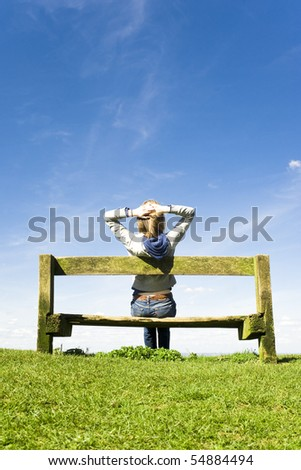 Young Woman Relaxing On A Park Bench On A Clear Summers Day - stock photo