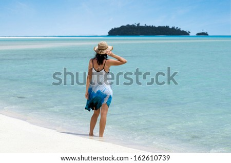 Young woman relaxing on Aitutaki Lagoon Cook Islands. Concept photo of women freedom, travel, vacation ,happy, happiness, solo, alone, single, fun.