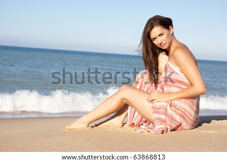 Young Woman Relaxing On Beach Wearing Wrap
