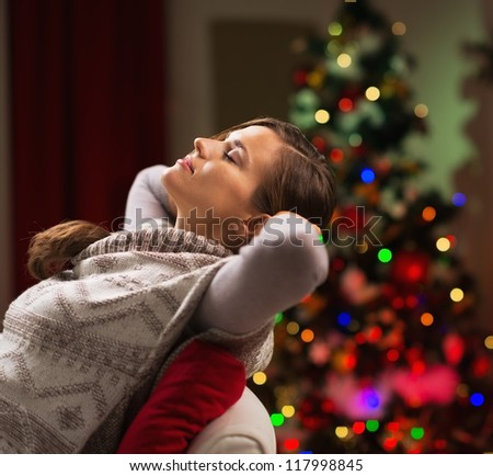 Young woman relaxing on chair in front of Christmas tree - stock photo