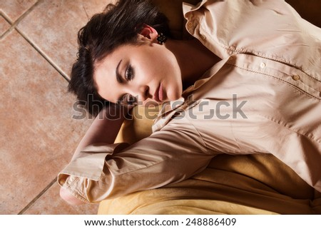 Young woman relaxing on couch in living room - stock photo