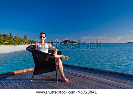 Young woman relaxing on deck overlooking tropical lagoon