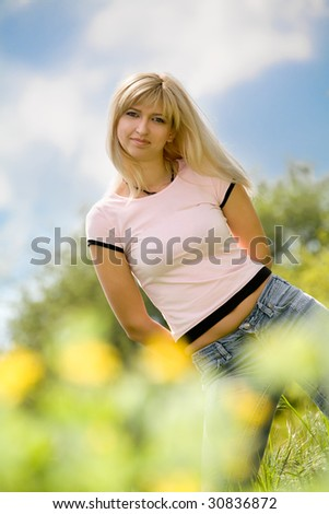 Young woman relaxing on green meadow under blue sky