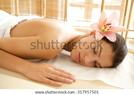 Young woman relaxing on massage table, eyes closed - stock photo