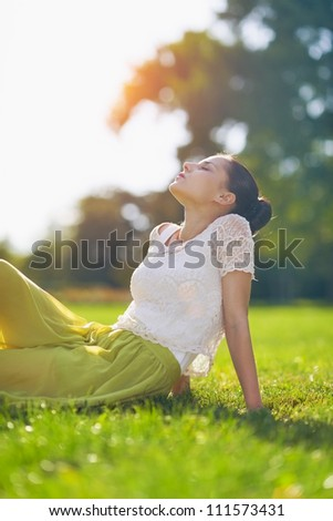 Young woman relaxing on meadow - stock photo