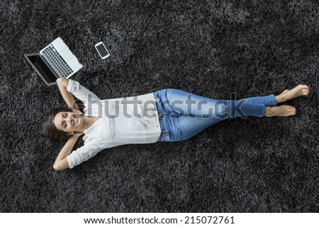 Young woman relaxing on the carpet - stock photo