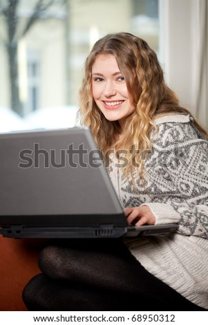 Young woman relaxing on the couch surfing - stock photo