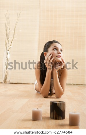 Young woman relaxing on the floor, after yoga excercises - stock photo