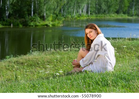 Young woman relaxing on the shore of lake.