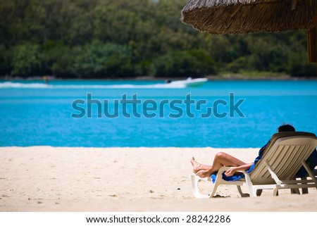 Young woman relaxing on tropical white sand beach. - stock photo