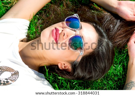 Young Woman relaxing outdoors looking happy and smiling - stock photo