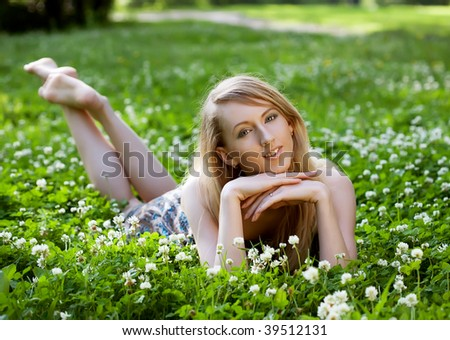 young Woman relaxing outdoors smiling - stock photo