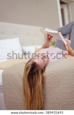 Young woman relaxing reading a book on a bed lying on her back with her long blond hair dangling over the edge