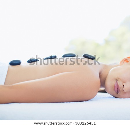 Young woman relaxing stone massage on spa treatment - stock photo