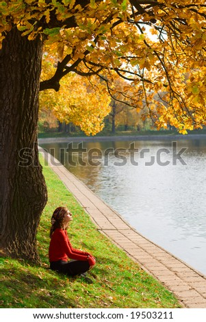 Young woman relaxing under a tree by the pool - stock photo