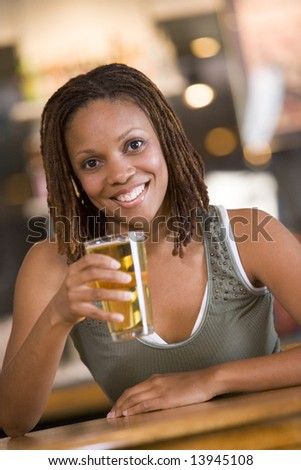 Young woman relaxing with a beer at a bar - stock photo