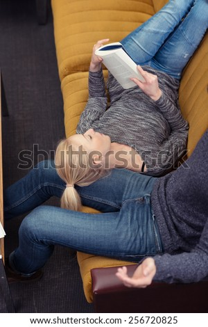 Young woman relaxing with a book at home lying back on the sofa with her head resting on her husbands leg, view from above