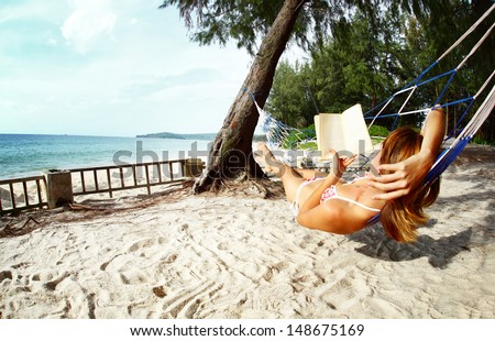 Young woman relaxing with a book in hammock on tropical beach - stock photo