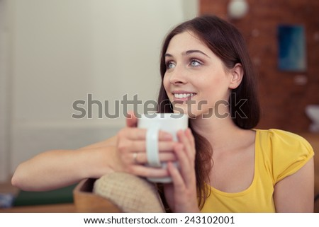 Young woman relaxing with a mug of coffee sitting in a comfortable chair daydreaming and looking into the air with a smile - stock photo
