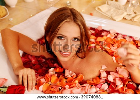 Young woman relaxing with rose petals  bath in spa saloon. Spa procedure. - stock photo