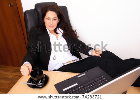 Young woman relaxing with the feet up on the desk - stock photo