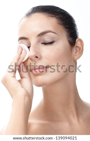 Young woman removing eye makeup by cotton pad eyes closed. - stock photo