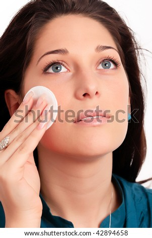 Young woman removing makeup with cleansing pad - stock photo