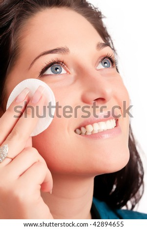 Young woman removing makeup with cleansing pad isolated on white - stock photo