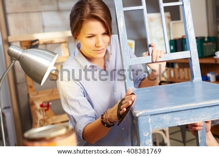 Young woman renewing chair, grinding. - stock photo