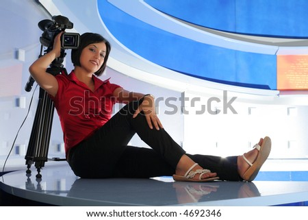 Young woman reporter posing like a photo model in TV studio
