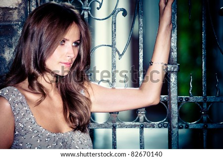 young woman rest upon a wrought iron entrance gate - stock photo