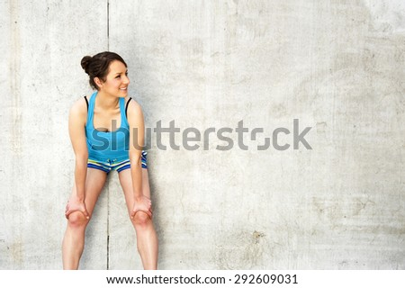 young woman resting after run by the wall in city. in blue sportswear. - stock photo