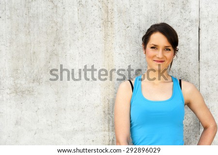 young woman resting after run by the wall in city with big smile. in blue sportswear. - stock photo