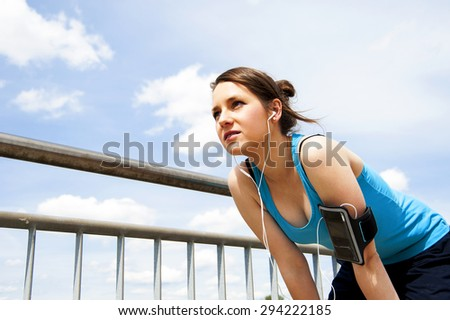 young woman resting after run. in blue sportswear. over the sky - stock photo