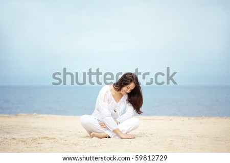 Young woman resting at beach near the sea